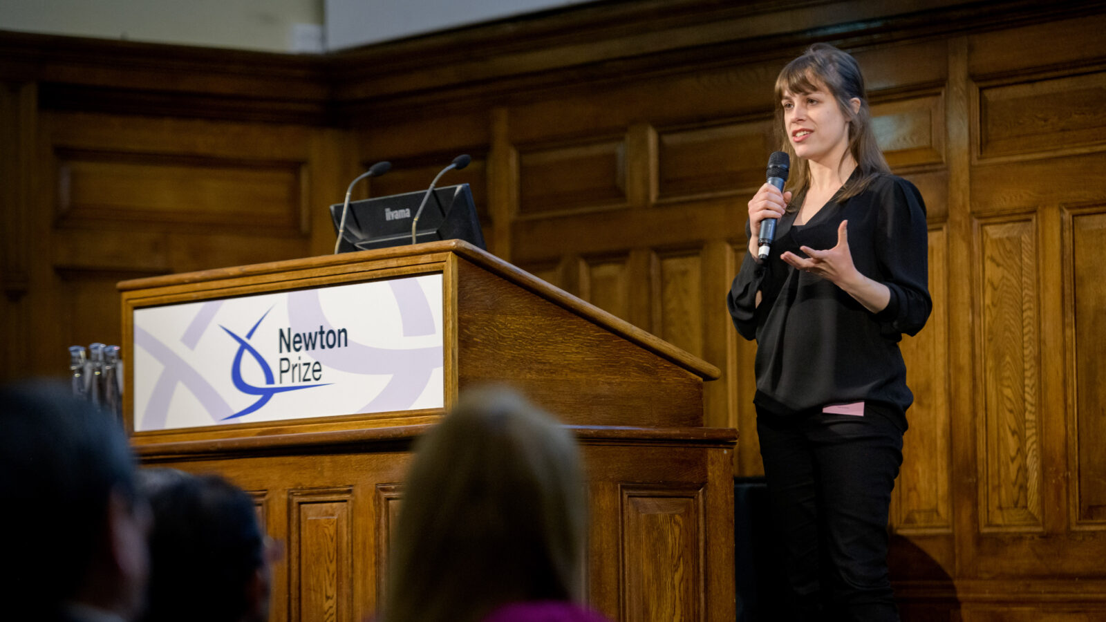 Host stands on stage at Newton Prize