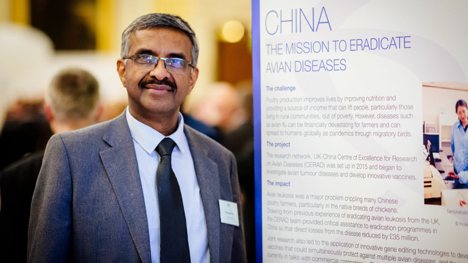 Image of researcher next to 2019 Newton Prize poster