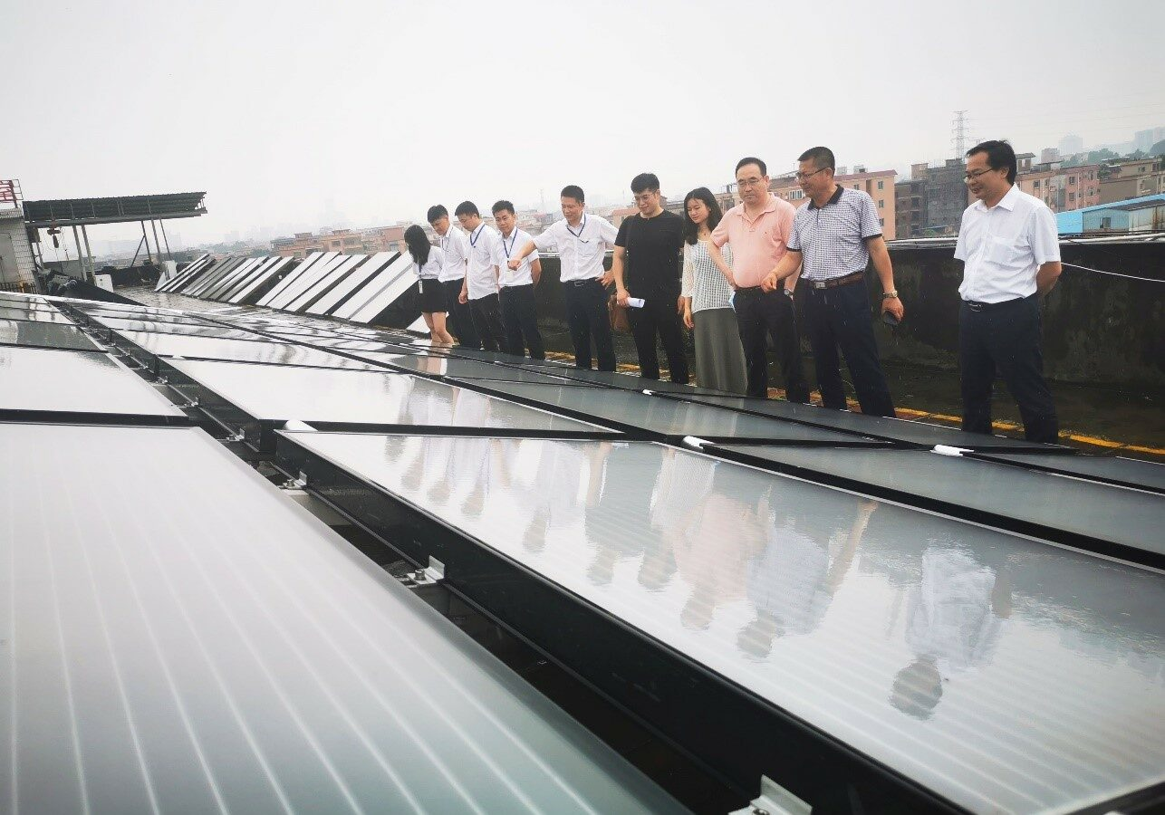 Line of people in front of solar panels