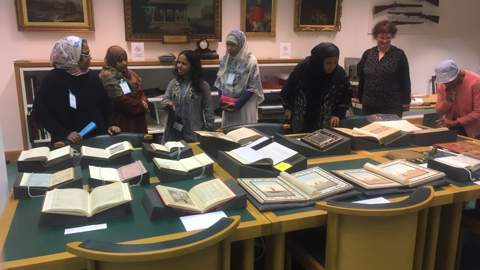 Women looking at ancient Bengali books laid out on a table