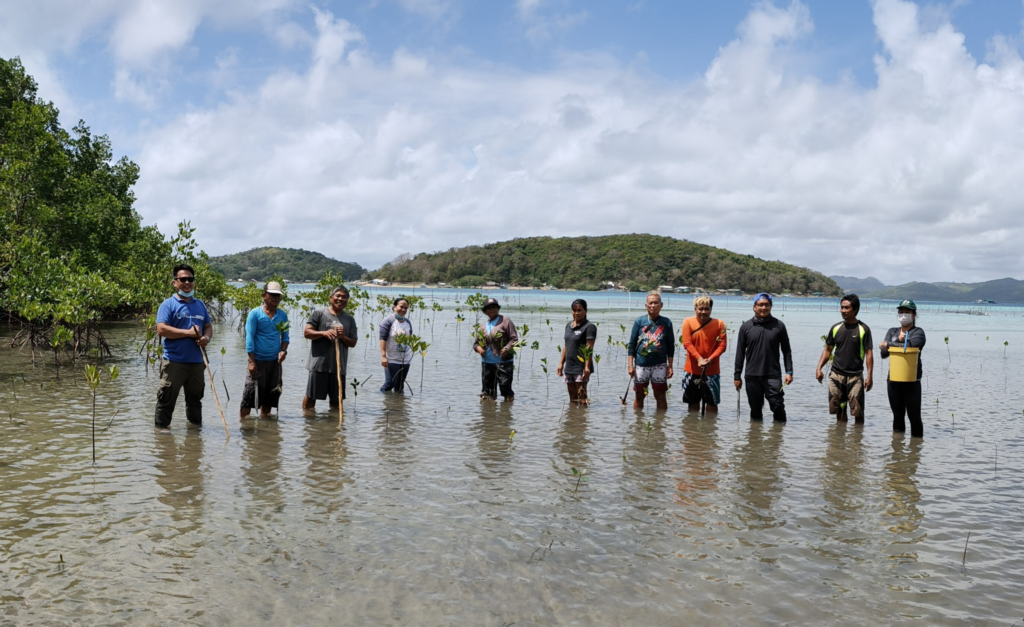 Villagers and local leaders taking a quick rest for photos during the community-led mangrove planting